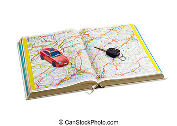 Car key and toy car on the open road atlas