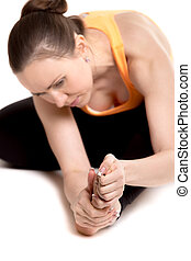 Young female athlete rubbing sore foot