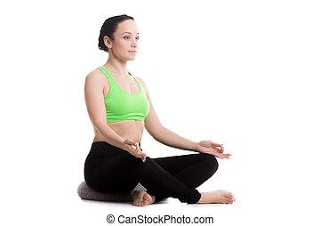 Sukhasana yoga pose with pillow - Serene girl practicing...