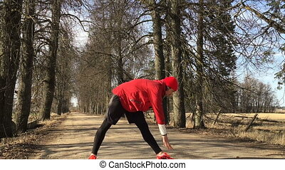 Man the athlete does exercises on opened air before run Slow...
