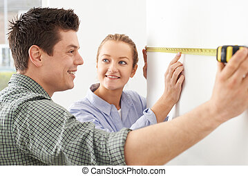 Young Couple Measuring Wall In New Home