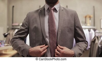 young man trying suit jacket at clothing store