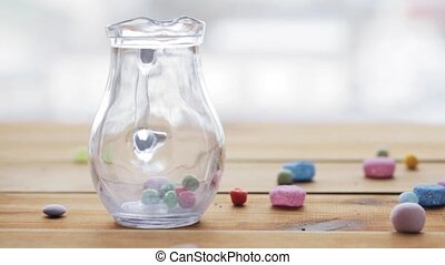 close up of hand dropping jelly candies to jug - food,...