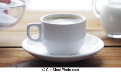 hand pouring sugar by teaspoon into coffee cup - unhealthy...