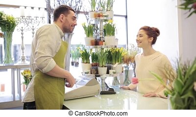 florist showing flowers to woman at flower shop - people,...