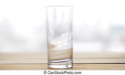 lemonade or soda drink pouring into glass on table -...