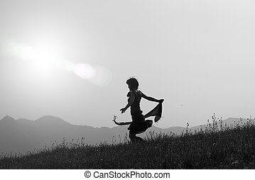 Free young girl in nature with scarf in the wind. black and...
