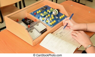 Girl drawing the scheme of electric circuit in the book,...