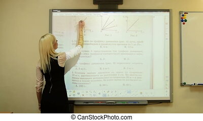 Young teacher working with interactive whiteboard - Young...