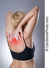 Woman with backache. Pain in the human body on a gray...