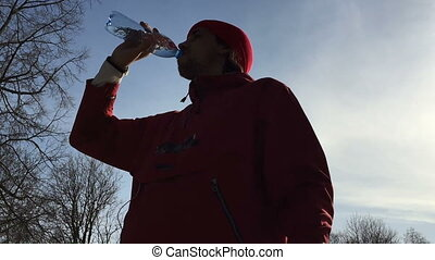 Silhouette of sportsman drinks water from a bottle.