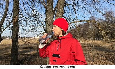 Sportsman drinks water from a bottle in the open air.