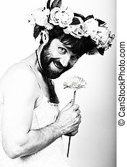 bearded man in a woman's wedding dress on, holding a flower. on his head a wreath of flowers. funny bearded bride, black and white