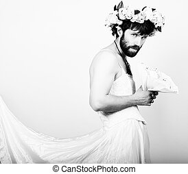 bearded man in a woman's wedding dress on her naked body, holding a flower. on his head a wreath of flowers. funny bearded bride, black and white
