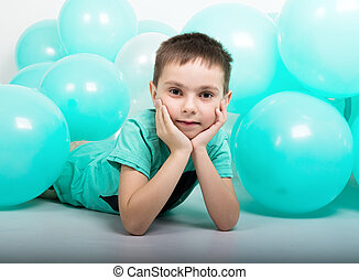 young man lying on the floor, around him are balloons.