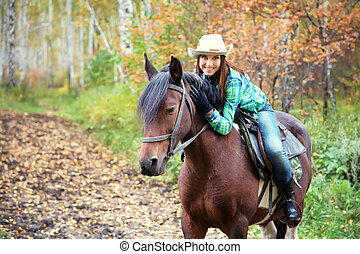 woman riding a horse - Attractive smiling woman in a hat...