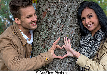 enamoured couple behind a tree - a young, laughed liebtes...