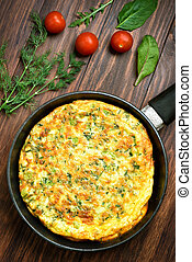 Omelette in frying pan on wooden background, top view