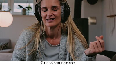 Smiling happy woman relaxing with her music at home sitting...