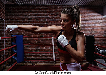 Strenght - Young woman in boxing ring