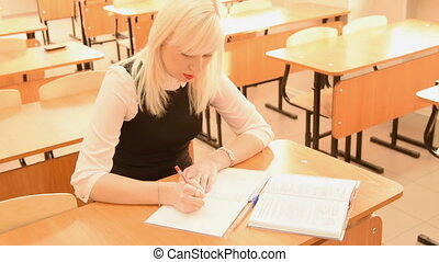 Student taking notes from textbook - Young female student...