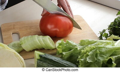 Chef cuts ripe tomato fruit for a garden salad