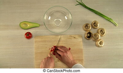 Top view of chef finely cuts red bell pepper - Cooking food....