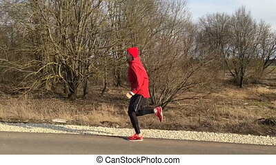 Sportsman in red clothes runs on the park alley the camera...