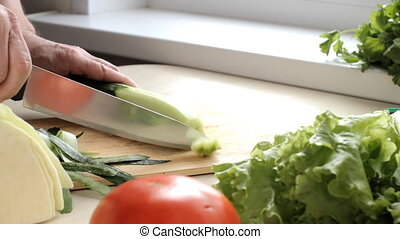 Man slicing green cucumber on the wooden cutting board.