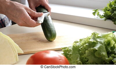 Peeling a cucumber on the wooden cutting board
