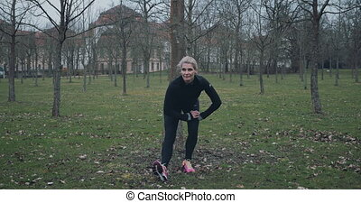 Fit middle-aged woman doing exercises in the park to stretch...