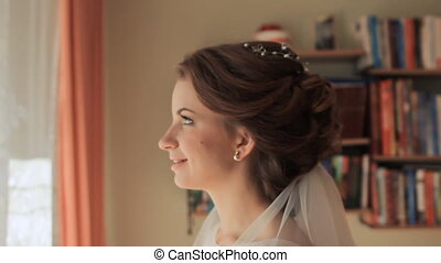 Bride touches an artificial butterfly on the window