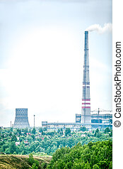Factory with smoking chimneys and green trees in front