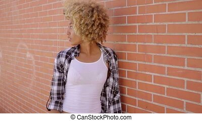 Woman Walking Along A Brick Wall. - Young black attractive...