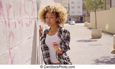 Woman Walking Along A Stone Wall. - Young mixed-race woman...