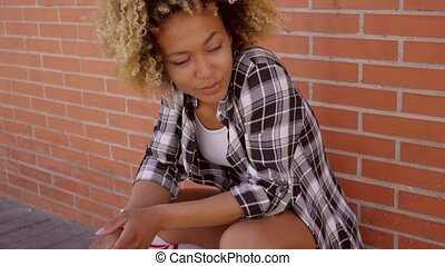 Young Girl Crouching - Young lady crouching against brick...
