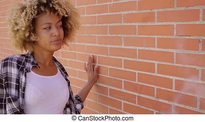 Woman Walking Along A Brick Wall - Young black attractive...