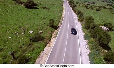 Aerial View Of Driving Car - Camera follows with distance...