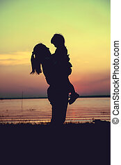 Silhouette of mother and child enjoying the view at riverside. Cross process. Vintage style.