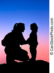 Silhouette side view of mother and child hikers enjoying the view at the top of a mountain.
