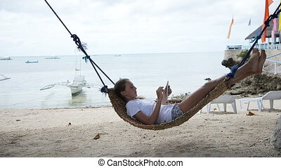 Girl in the hammock with the tablet on the beach - Young...