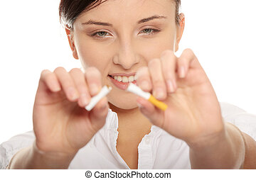 Don't smoke - Young woman breaking cigarette over white...