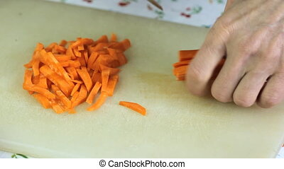 We cut carrots. close up on woman's hand slicing carrot on...