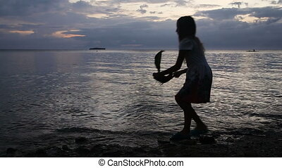 Young girl playing with toy ship on the beach - Happy child...