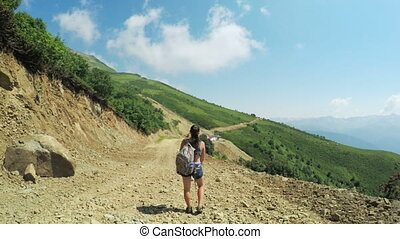 Girl tourist in mountains - In mountain raises woman with...