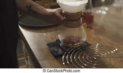 Barista of coffee shop makes a cup of coffee for the visitor...