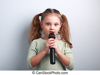 Cute fun kid girl singing song in microphone on blue background. Young talent