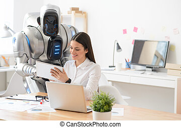 Pleasant girl and robot using tablet - Work together....