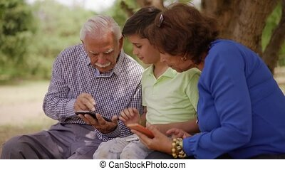 17-Boy Helping Grandpa Surfing Internet On Mobile Phone -...