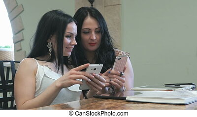 Two girls are watching photos on a mobile phone